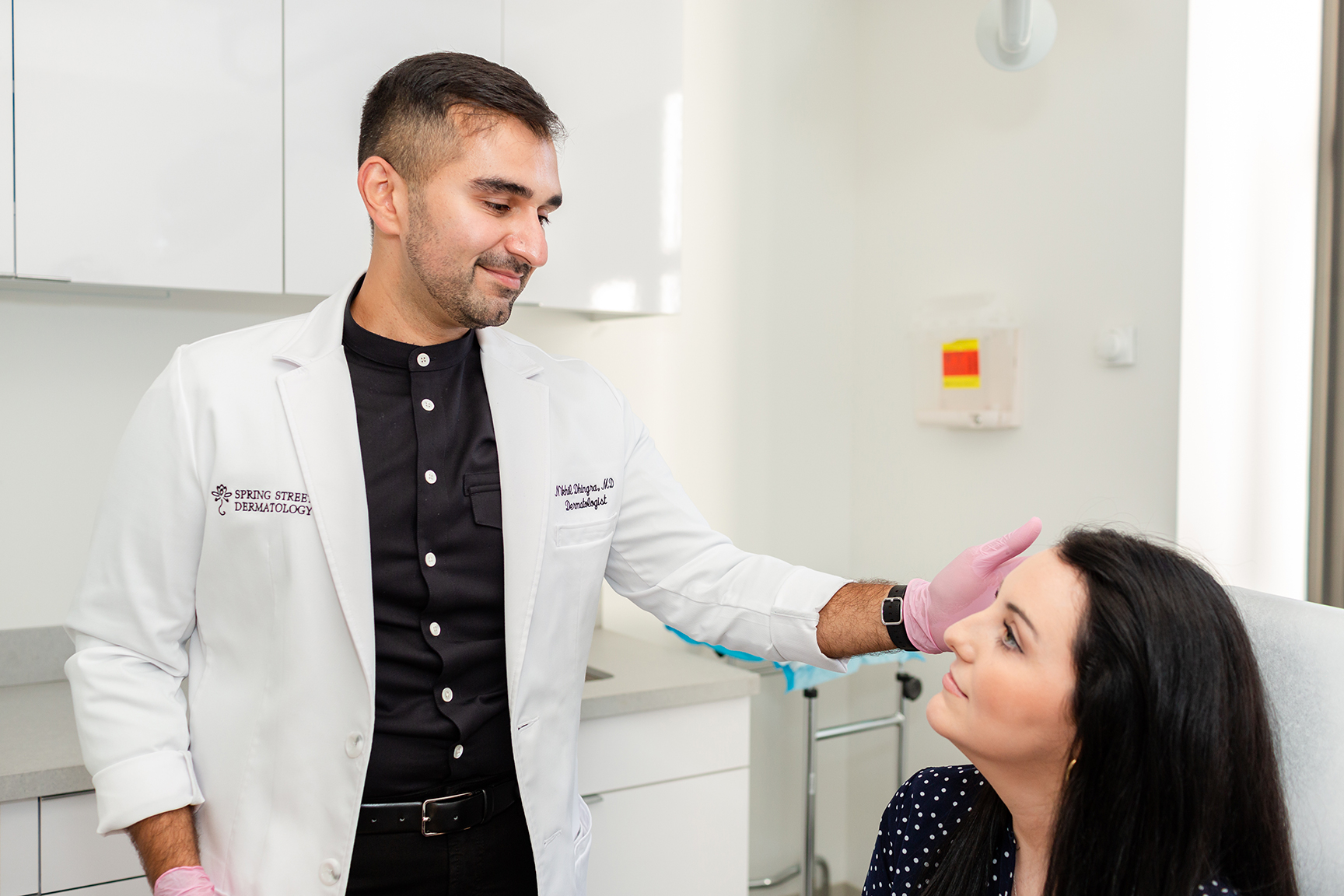 Image showing Dr. Dhingra, board certified dermatologist checking his patient  for cosmetic treatments at Spring Street Dermatology, New York City, NY