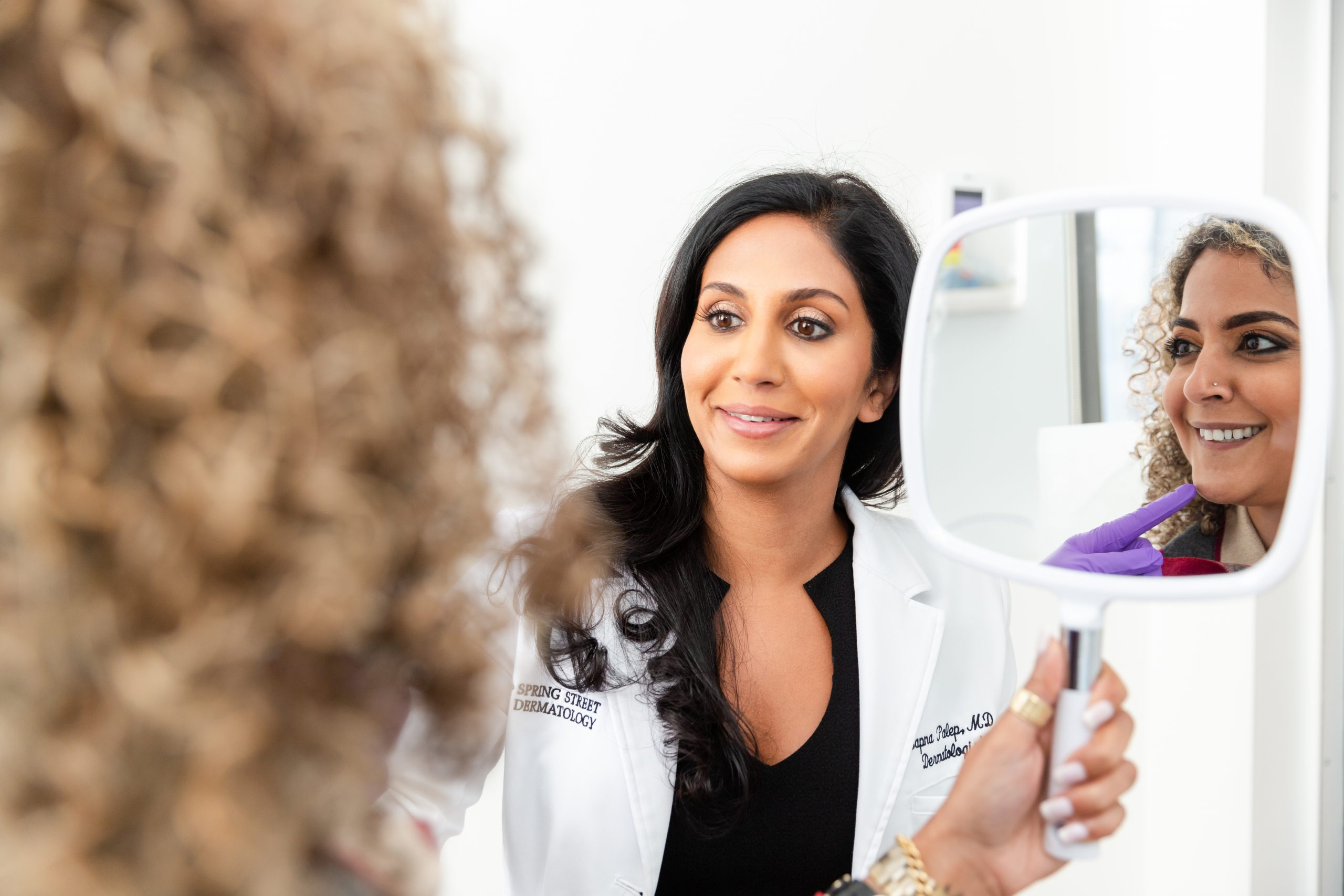 Board Certified Dermatologist Dr. Sapna Palep letting her patient see the results in the mirror, rosacea treatment in New York, NY.
